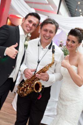 saxophonspieler auf einer hochzeit mit dem brautpaar zusammen