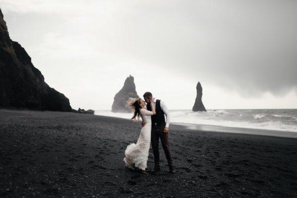 brautpaar am meer in schwarz weiss macht ein fotoshooting