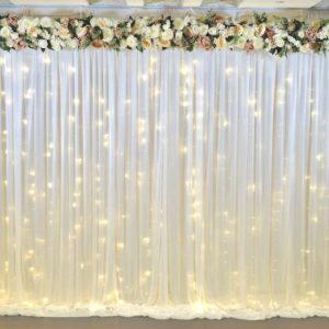 Fotowand und Rückwand als Rück Abdeck Wand mit Stoff und Blumen für Hochzeit mieten mit Lichterketten Verleih von StasEvents leihen als Hochzeitsdeko Vorschau