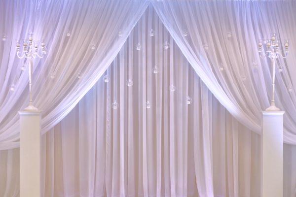 Fotowand und Rückwand als Wand mit hängenden Teelichter und Blumen für Brautpaartisch mieten als Hochzeitsdeko leihen Modell Kira von StasEvents 1